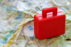Mini red suitcase on a jammed a map. Closeup Royalty Free Stock Images