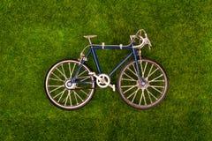 Mini retro blauwe stuk speelgoed fiets op grasweide Stock Fotografie