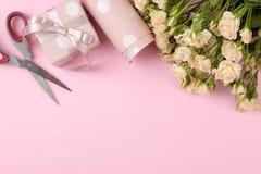 Mini rosas hermosas con la caja de regalo y el documento de embalaje rosados sobre un fondo rosado brillante holidays Día del `s  fotografía de archivo