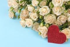 Mini rosas hermosas con un corazón rojo en un fondo azul brillante holidays Día del `s de la tarjeta del día de San Valentín Prim fotografía de archivo libre de regalías