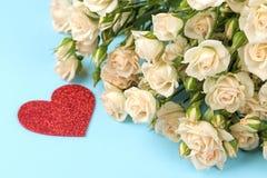 Mini rosas hermosas con un corazón rojo en un fondo azul brillante holidays Día del `s de la tarjeta del día de San Valentín Prim foto de archivo
