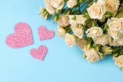 Mini rosas hermosas con un corazón rosado en un fondo azul brillante holidays Día del `s de la tarjeta del día de San Valentín Pr imagenes de archivo