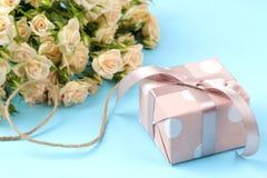 Mini rosas hermosas con una caja de regalo rosada en un fondo azul brillante holidays Día del `s de la tarjeta del día de San Val fotografía de archivo libre de regalías