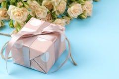 Mini rosas hermosas con una caja de regalo rosada en un fondo azul brillante holidays Día del `s de la tarjeta del día de San Val imagen de archivo libre de regalías