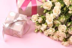 Mini rosas hermosas con una caja de regalo rosada en un fondo rosado brillante holidays Día del `s de la tarjeta del día de San V foto de archivo