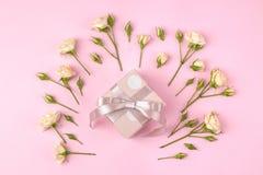 Mini rosas hermosas con una caja de regalo rosada en un fondo rosado brillante holidays Día del `s de la tarjeta del día de San V fotografía de archivo libre de regalías