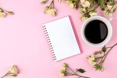 Mini rosas hermosas con una taza de café y de un cuaderno en un fondo rosado brillante holidays Día del `s de la tarjeta del día  imagen de archivo