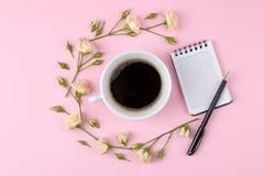 Mini rosas hermosas con una taza de café y de un cuaderno en un fondo rosado brillante holidays Día del `s de la tarjeta del día  fotos de archivo libres de regalías