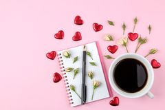 Mini rosas hermosas con una taza de café y de un cuaderno en un fondo rosado brillante holidays Día del `s de la tarjeta del día  foto de archivo