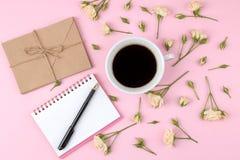 Mini rosas hermosas con una taza de café y de un cuaderno en un fondo rosado brillante holidays Día del `s de la tarjeta del día  fotografía de archivo