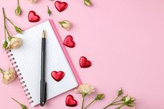 Mini rosas hermosas con una taza de café y de un cuaderno en un fondo rosado brillante holidays Día del `s de la tarjeta del día  foto de archivo libre de regalías