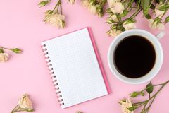 Mini rosas hermosas con una taza de café y de un cuaderno en un fondo rosado brillante holidays Día del `s de la tarjeta del día  imágenes de archivo libres de regalías