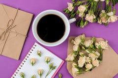 Mini rosas hermosas en un sobre con una libreta y una taza de café en un fondo brillante de la lila holidays Día del `s de la tar imagen de archivo libre de regalías