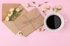 Mini rosas hermosas a la taza de café y un sobre en un fondo rosado brillante holidays Día del `s de la tarjeta del día de San Va imagen de archivo libre de regalías
