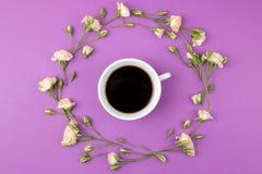 Mini rosas hermosas y una taza de café en un fondo brillante de la lila holidays Día del `s de la tarjeta del día de San Valentín foto de archivo