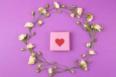 Mini rosas y caja de regalo hermosas en un fondo brillante de la lila holidays Día del `s de la tarjeta del día de San Valentín D imagenes de archivo
