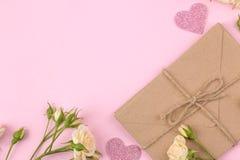 Mini rosas y sobre hermosos en un fondo rosado brillante holidays Día del `s de la tarjeta del día de San Valentín Día del `s de  imágenes de archivo libres de regalías