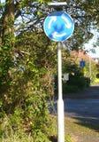 Mini Roundabout Sign United Kingdom em um ajuste urbano foto de stock