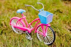 Mini roze stuk speelgoed fiets op gras Fiets op weide de reissport van de de lentezomer Actieve levensstijl Royalty-vrije Stock Afbeelding