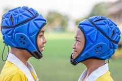 Two Face of Mini Rugby boys player. Mini Rugby match, Vajiravudh College, Bangkok, Thailand - November 2018 : Two boys wear rugby helmet looking each other ready stock images