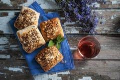 Mini rustikales Brot mit dem Leinsamen auf einem blauen Leinen mit lavander Blumen und rosafarbenem Wein Stockfotos