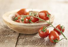 Mini san Marzano vine tomatoes. Bunch of ripe fresh mini san Marzano vine tomatoes displayed half in half out of a small wooden dish over a wood background Stock Image