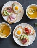 Mini sanduíches com queijo creme, vegetais, ovos de codorniz, salame e chá verde com limão e tomilho Sanduíches com queijo, cucu foto de stock royalty free