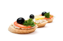 Mini sandwiches. Bread with cream cheese, tomato, lemon, olives and parsley Stock Photography
