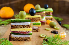 Mini sandwiches canape with fresh cucumbers, ham, cheese, olives, salami, black bread on a cutting board. Royalty Free Stock Photography