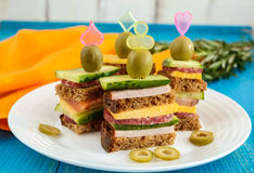 Mini sandwiches canape with fresh cucumbers, ham, cheese, olives, salami, black bread Stock Image