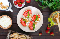 Mini sandwiches with cottage cheese, fresh strawberries, decorated with mint leaves Royalty Free Stock Images
