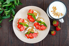 Mini sandwiches with cottage cheese, fresh strawberries, decorated with mint leaves Stock Photography