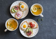 Mini sandwiches with cream cheese, vegetables, quail eggs, salami and green tea with lemon and thyme. Sandwiches with cheese, cucu Royalty Free Stock Image