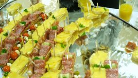 Mini sandwiches on a mirrored circular surface at the event, sandwiches with small meals. Tasting ingredients, ham, tuna. Salmon and various spreads, sausages stock footage
