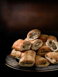 Mini Sausage Rolls. Mini cocktail sausage rolls stacked on a pewter plate against a dark rustic background. Generous accommodation for copy space stock photography