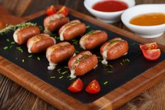 Mini sausages stuffed with cheese and baked on wooden background Royalty Free Stock Photo
