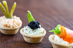 Mini savory tartlets on wooden surface. Royalty Free Stock Images