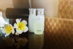 Mini set shampoo and bath soap liquid amd conditioner gel with f. Lowers plumeria or frangipani on black counter in vintage relaxing and spa mood, classic and Stock Photos