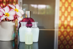 Mini set shampoo and bath soap liquid amd conditioner gel with f. Lowers plumeria or frangipani on black counter in vintage relaxing and spa mood, classic and Stock Image