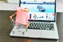 Mini Shopping Cart with Mini Shopping Bags on Laptop with E-Commerce Website on the Screen stock photography