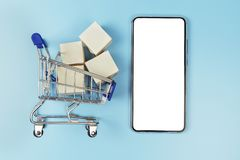 Mini shopping cart with cardboard boxes. Smartphone for mockup purposes isolated on white background stock photography