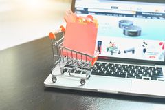 Mini Shopping Cart Filled with Shopping Bags Isolated on Wooden Table with Keyboard as for E-Commerce stock photos