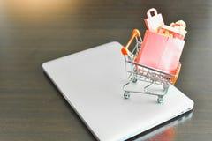 Mini Shopping Cart Filled com Mini Shopping Bags Isolated em um portátil quanto para ao comércio eletrônico imagem de stock