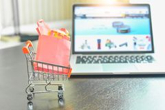 Mini Shopping Cart Filled com os sacos de compras isolados no portátil com Amazonas Web page de COM foto de stock