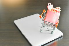 Mini Shopping Cart Filled with Mini Shopping Bags Isolated on a Laptop as for E-Commerce stock image