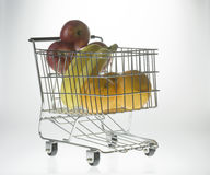 Mini Shopping Cart With Fruit. Mini shopping cart as a fruit basket or grocery cart holding oranges, apples and bananas in front of a gradient white background Stock Photography
