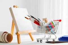 Mini shopping cart full with artistic goods and canvas on easel. Mini shopping cart full with artistic goods for drawing, artist canvas and easel. Art shop Royalty Free Stock Image