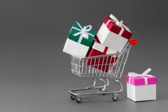 Mini shopping cart full of colorful gift boxes with ribbons. Royalty Free Stock Images