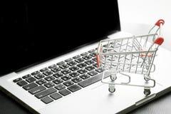 Mini Shopping Cart On Laptop con il processo filtrato immagini stock libere da diritti