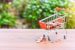 Mini Shopping Cart o carretilla para el comercio al por menor llenado de las monedas de bronce aisladas en la tabla de madera imagen de archivo